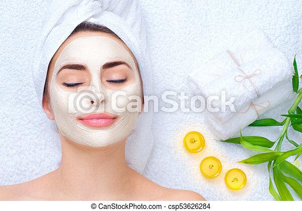 Mujer spa aplicando máscara facial. Retrato de una hermosa chica con una toalla en la cabeza aplicando una máscara de arcilla facial - csp53626284