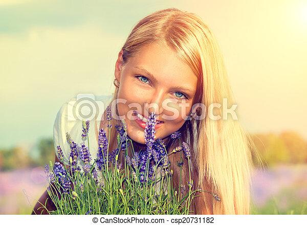 Hermosa chica con flores en el campo de lavanda - csp20731182