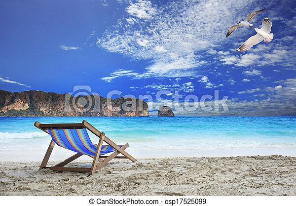 Sillas de madera playa en el lado del mar con hermosas gaviotas volando sobre el cielo azul y la isla de piedra en línea horizontal con el océano como vacaciones y fondo natural de vacaciones - csp17525099