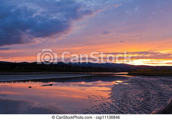 Hermosa puesta de sol sobre el río Yukon cerca de Dawson City - csp11136846