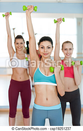 Entrenamiento de peso. Tres bellas mujeres en ropa deportiva ejercitándose con pesas y sonriendo a la cámara - csp19251237