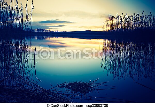 Una foto antigua de una hermosa puesta de sol sobre un lago tranquilo - csp33883738