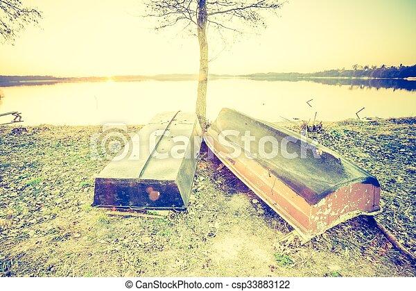 Una foto antigua de una hermosa puesta de sol sobre lagos tranquilos y barcos de pescadores - csp33883122