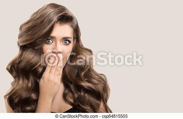 Retrato de una hermosa mujer linda con cabello castaño rizado. Antecedentes grises. - csp64815503