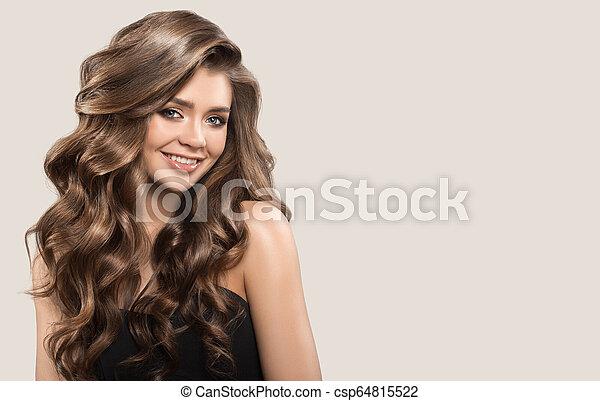 Retrato de una hermosa mujer linda con cabello castaño rizado. Antecedentes grises. - csp64815522