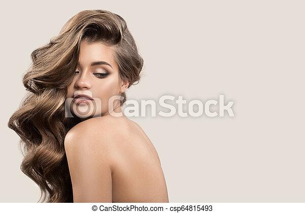 Retrato de una hermosa mujer linda con cabello castaño rizado. Antecedentes grises. - csp64815493