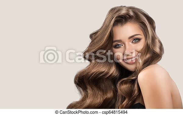 Retrato de una hermosa mujer linda con cabello castaño rizado. Antecedentes grises. - csp64815494