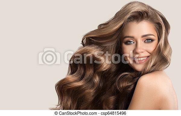 Retrato de una hermosa mujer linda con cabello castaño rizado. Antecedentes grises. - csp64815496
