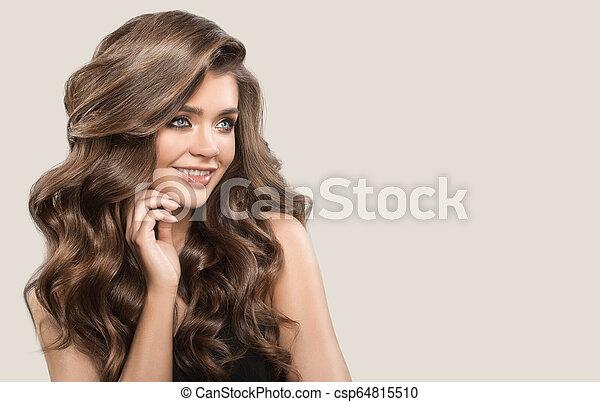 Retrato de una hermosa mujer linda con cabello castaño rizado. Antecedentes grises. - csp64815510
