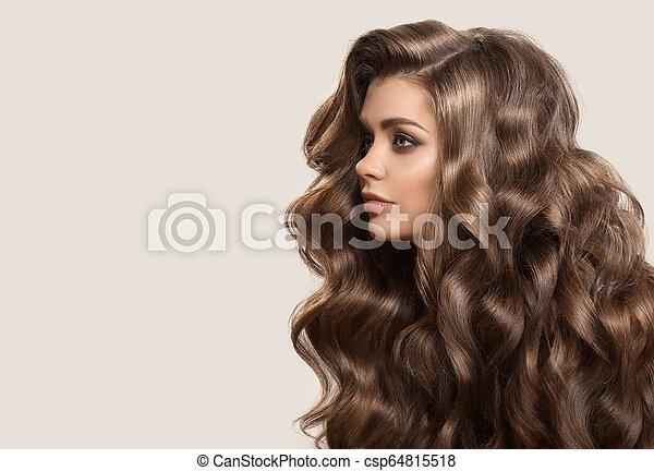 Retrato de una hermosa mujer linda con cabello castaño rizado. Antecedentes grises. - csp64815518