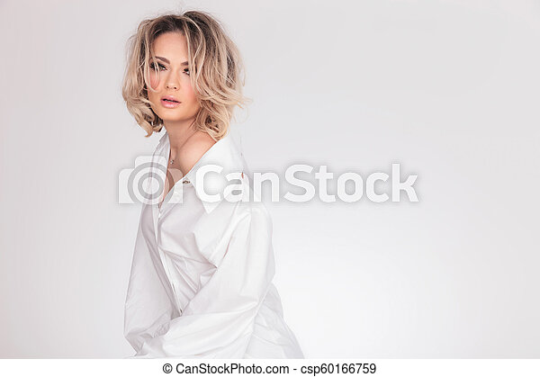 Hermosa mujer llevando una camisa blanca grande con cuello