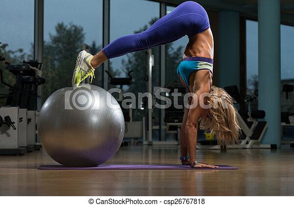 Hermosa mujer haciendo pike con pelota de estabilidad - csp26767818