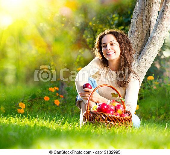 Hermosa chica comiendo manzana orgánica en el huerto - csp13132995