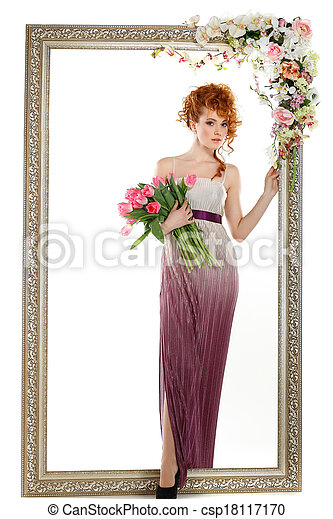 Hermosa chica pelirroja con el ramo de tulipanes, que está en un marco de oro, florecida, aislada en un fondo blanco - csp18117170