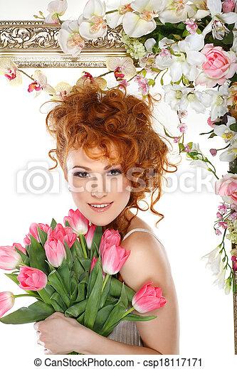 Hermosa chica pelirroja con el ramo de tulipanes, que está en un marco de oro, florecida, aislada en un fondo blanco - csp18117171