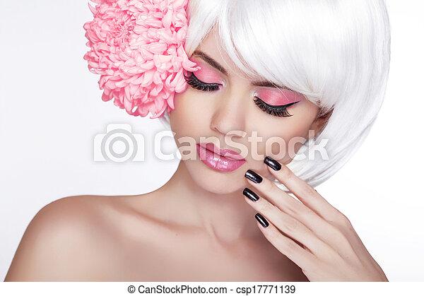 Retrato de mujer rubia con flor lila. Hermosa mujer del spa tocando su cara. Maquillaje y uñas manicuradas. Piel fresca perfecta. Aislado de fondo blanco - csp17771139
