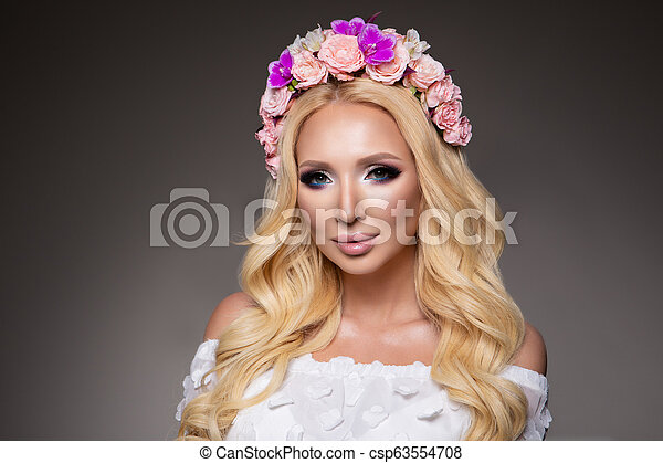 Hermosa mujer con el pelo rizado largo, maquillaje perfecto - csp63554708