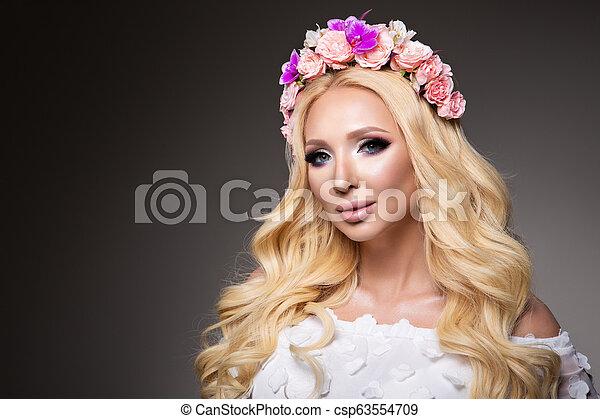 Hermosa mujer con el pelo rizado largo, maquillaje perfecto - csp63554709