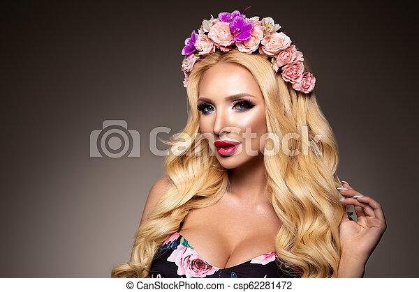 Hermosa mujer con el pelo rizado largo, maquillaje perfecto - csp62281472