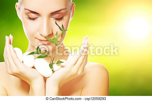 Hermosa joven sosteniendo planta creciendo a través de piedras - csp12059293