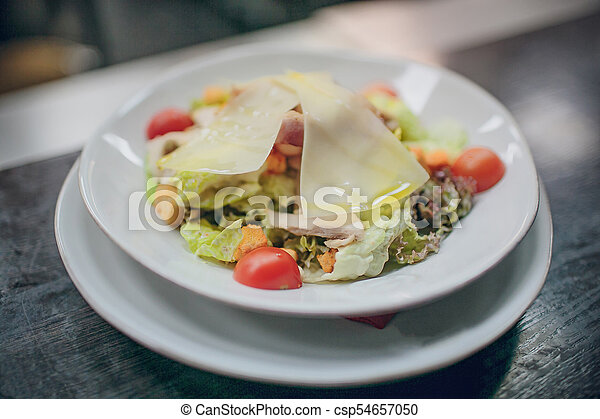 La comida en el restaurante está en un plato blanco - csp54657050