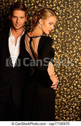 Hermosa pareja bien vestida parada contra la pared abstracta - csp17100470