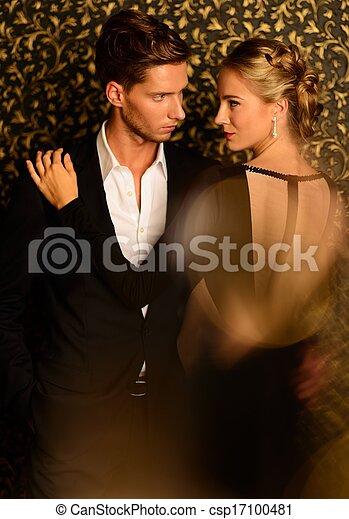 Hermosa pareja bien vestida parada contra la pared abstracta - csp17100481