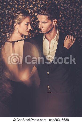 Hermosa pareja bien vestida parada contra la pared abstracta - csp20316688