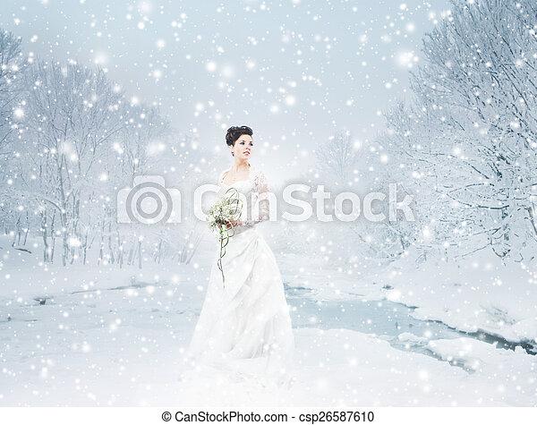 Una joven y hermosa novia parada con el ramo de flores - csp26587610