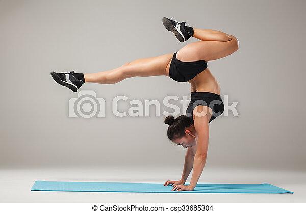 hermosa chica deportiva parada en pose de acróbata o asana