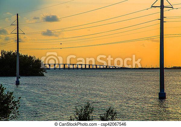 Hermosa puesta de sol colorida o amanecer con puente que lleva a Key West y cables eléctricos al lado - csp42067546