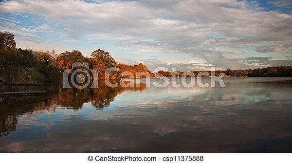 Hermosa puesta de sol sobre el lago Autumn Fall con un reflejo cristalino - csp11375888