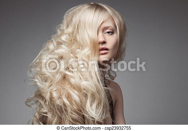 Hermosa mujer rubia. Cabello rizado y largo - csp23932755