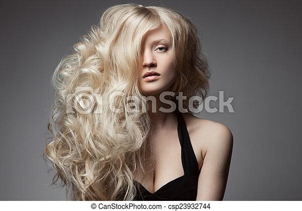 Hermosa mujer rubia. Cabello rizado y largo - csp23932744