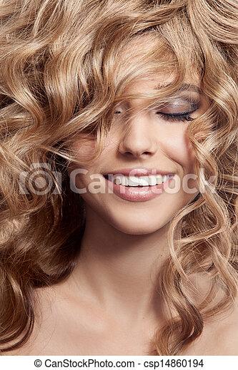 Hermosa mujer sonriente. Cabello largo y saludable rizado - csp14860194