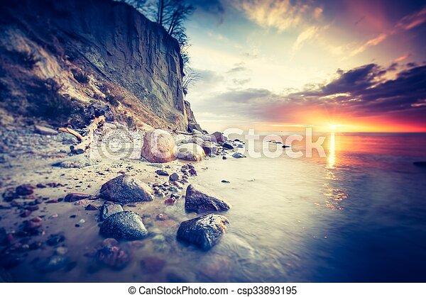 Una foto antigua de la hermosa playa rocosa al amanecer - csp33893195