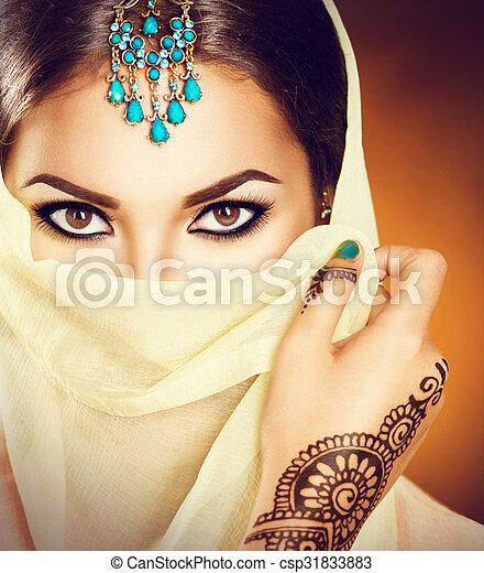 Hermosa mujer india con joyas turquesas tradicionales escondiendo su cara - csp31833883