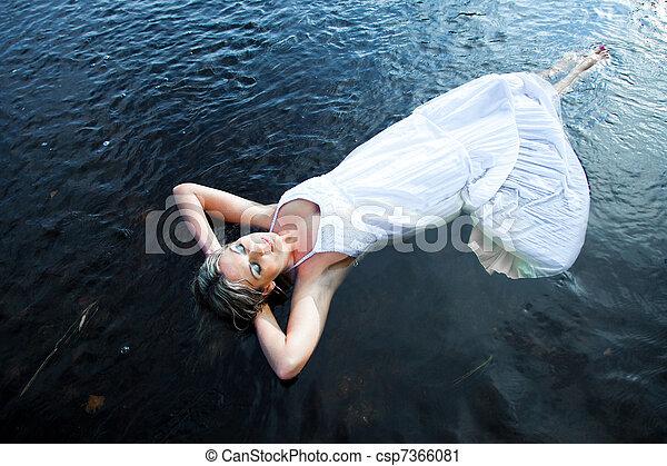 Retrato de bella mujer disfrutando del silencio y la soledad flotando en el río azul a primera hora de verano - csp7366081