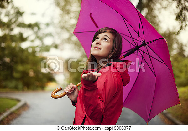 Hermosa mujer con paraguas buscando lluvia - csp13006377
