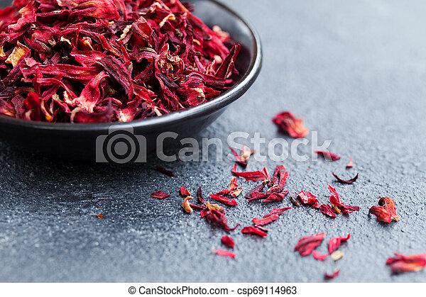 Hibiscus tea in black bowl. Slate background. Close up. Copy space. - csp69114963