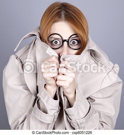 Hiding red-haired girl in glasses and cloak. - csp6051226