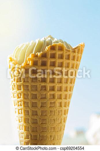 Cono de helado de vainilla contra el cielo azul y la luz del sol - csp69204554
