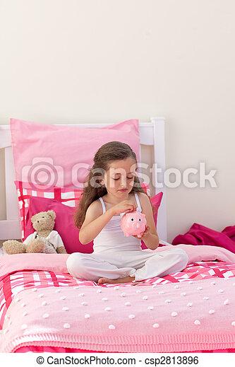 High angle of a little girl saving money in a piggybank - csp2813896