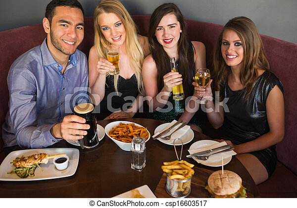 High angle view of happy friends having dinner together - csp16603517