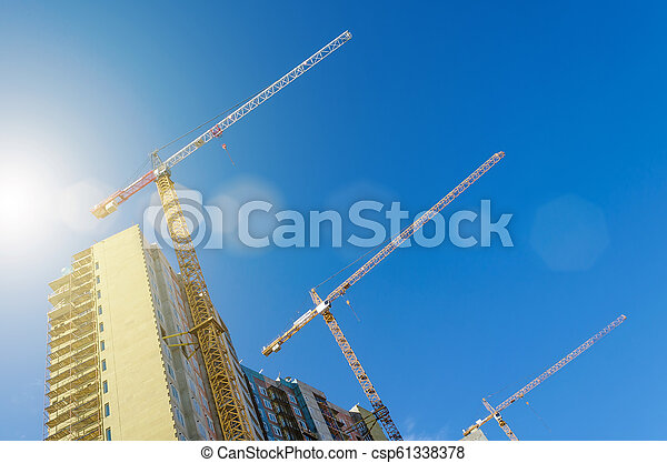High cranes on the construction of residential buildings, against the blue sky. - csp61338378