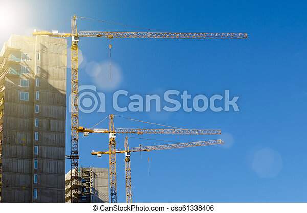 High cranes on the construction of residential buildings, against the blue sky. - csp61338406