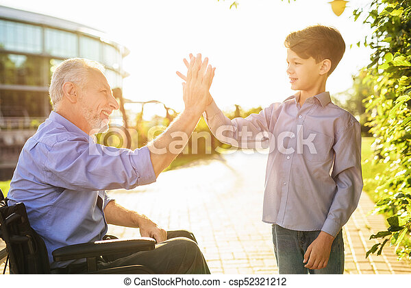 High five the old man in a wheelchair greets his grandson high high five the old man in a wheelchair greets his grandson csp52321212 m4hsunfo