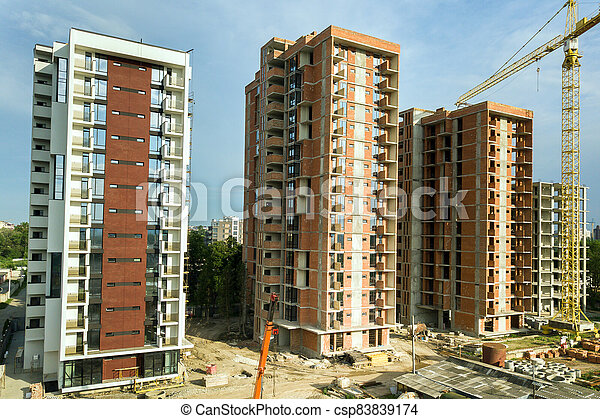 High-rise residential apartment buildings and tower crane under development on construction site. Real estate development. - csp83839174