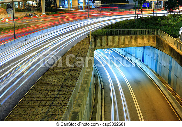 Highway in city at night with trails of car lights - csp3032601