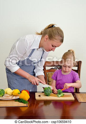 Madre e hija preparando comida. Cortando brócoli con cuchillo. - csp10659410